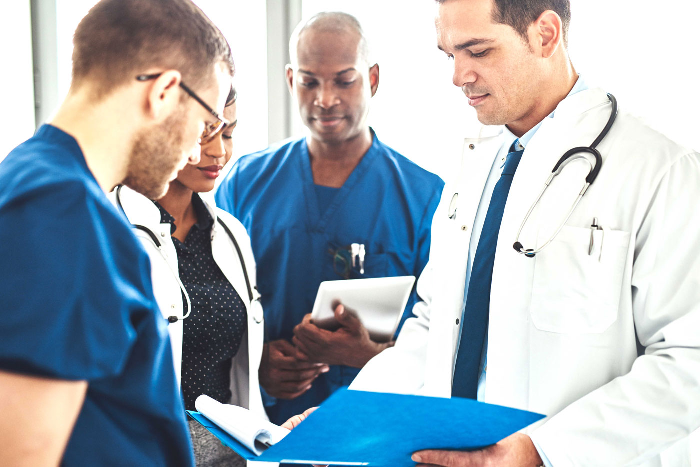 Doctors Standing In Circle Reviewing Paperwork